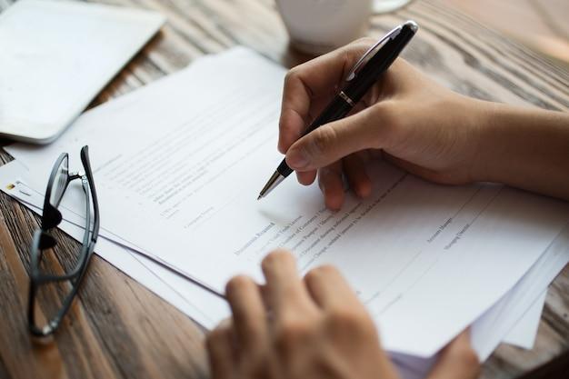 Zakenman het onderzoeken van papieren aan tafel
