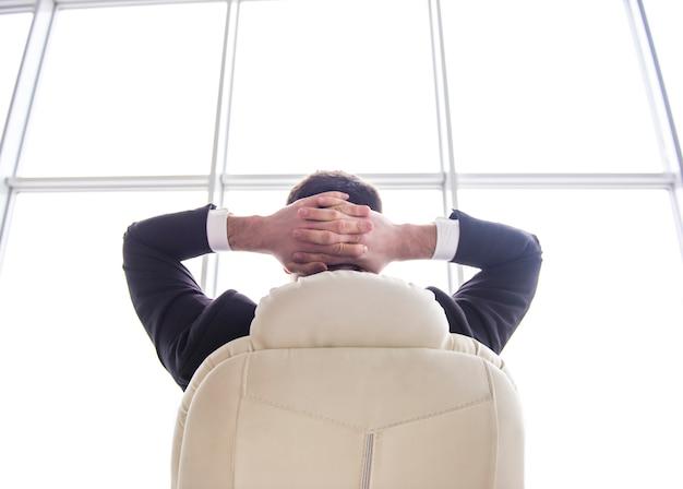 Zakenman het ontspannen als voorzitter van zijn bureau met zijn handen.