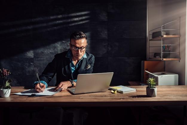 Zakenman het schrijven projectrapport in zijn kantoor