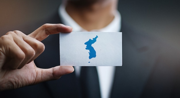 Zakenman holding card of unification vlag van korea vlag