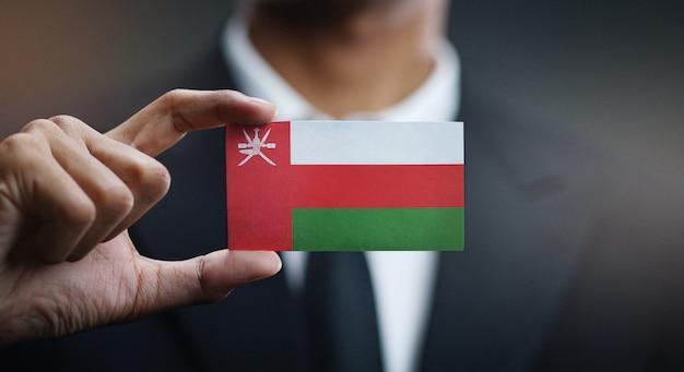 Zakenman holding card oman vlag