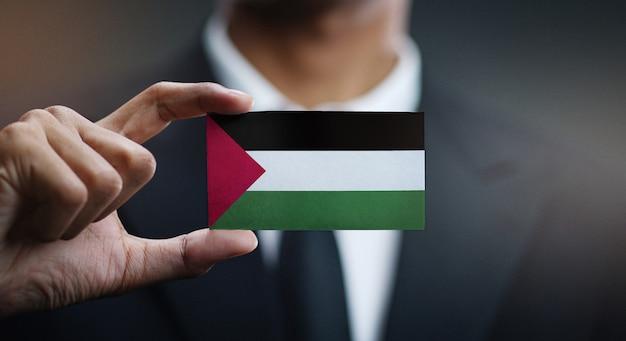 Zakenman holding card palestina vlag