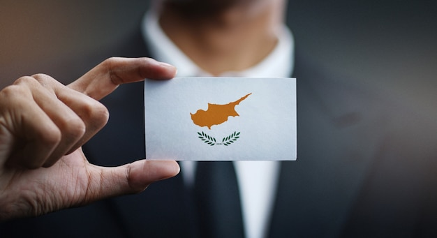 Zakenman holding card van cyprus vlag