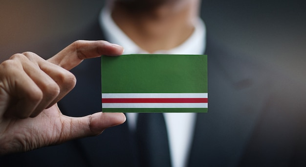 Zakenman holding card van de tsjetsjeense republiek ichkeria vlag