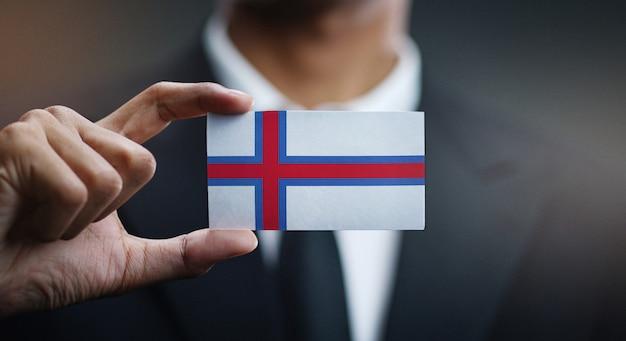 Zakenman holding card van de vlag van de faeröer