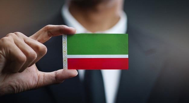 Zakenman holding card van de vlag van de tsjetsjeense republiek