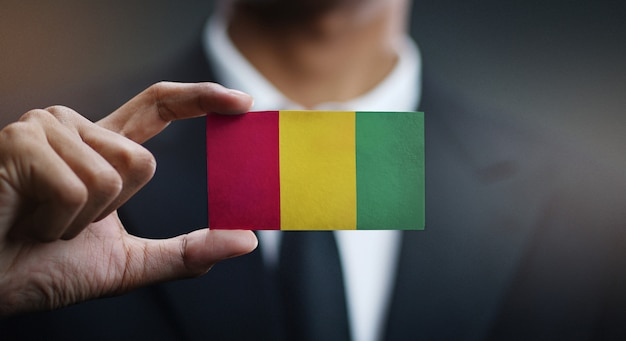 Zakenman holding card van de vlag van guinee