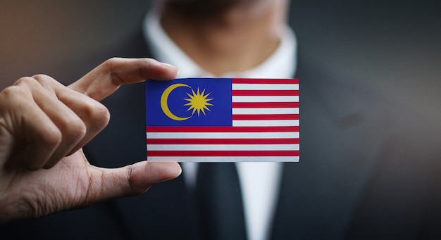 Zakenman holding card van de vlag van maleisië
