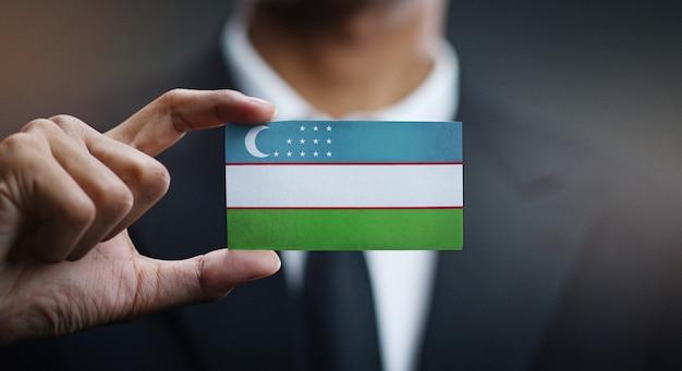 Zakenman holding card van de vlag van oezbekistan