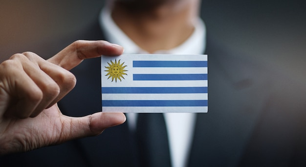 Zakenman holding card van de vlag van uruguay