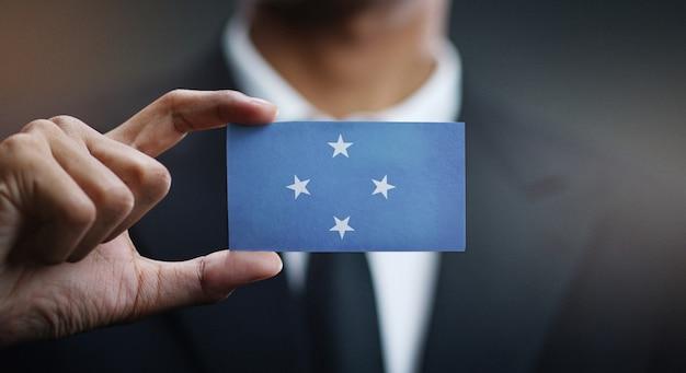 Zakenman holding card van federated states of micronesia flag