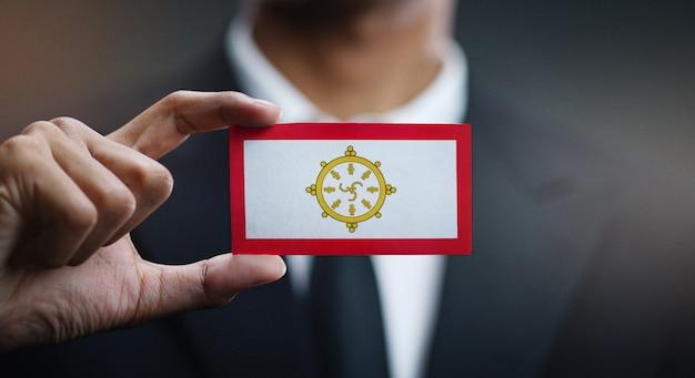 Zakenman holding card van sikkim flag