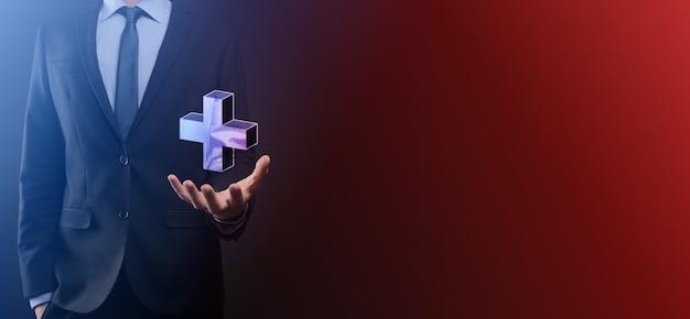 Zakenman houden 3d plus pictogram, man in de hand houden bieden positieve dingen zoals winst, voordelen, ontwikkeling, mvo vertegenwoordigd door plusteken. de hand toont het plusteken.