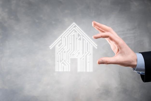 Zakenman houden huisje. slim huis gecontroleerd, intelligent huis en domotica app concept. pcb ontwerp en persoon met slimme telefoon. innovatietechnologie internet netwerkconcept.