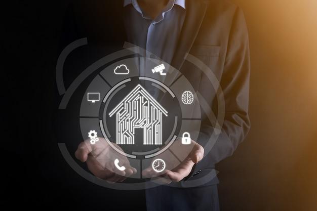 Zakenman houden huispictogram. smart home gecontroleerd, intelligent huis en domotica app concept. pcb-ontwerp en persoon met slimme telefoon. innovatie technologie internet netwerkconcept.
