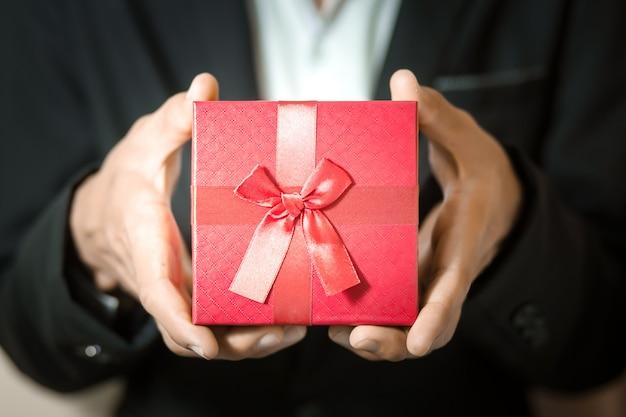 Zakenman houden rode geschenkdoos in handen.