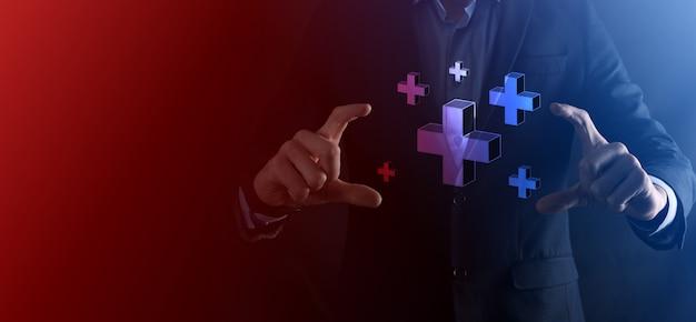 Zakenman houdt 3d plus-pictogram, man houdt in de hand bieden positieve dingen zoals winst, voordelen, ontwikkeling, mvo vertegenwoordigd door plusteken. de hand toont het plusteken.