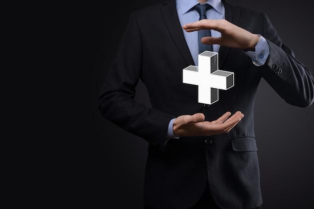 Zakenman houdt 3d plus-pictogram vast, man houdt in de hand biedt positieve dingen zoals winst, voordelen