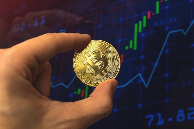 Zakenman houdt bitcoin op de achtergrond van de grafiekvoorraadgrafiek, crypto-uitwisseling en handelsconcept bedrijfsfoto