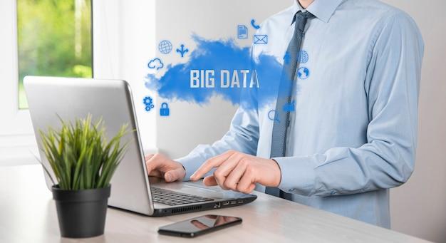 Zakenman houdt de inscriptie, woord big data. hangslot, hersenen, man, planeet, grafiek, vergrootglas, tandwielen, wolk, raster, document, brief, telefoonpictogram.