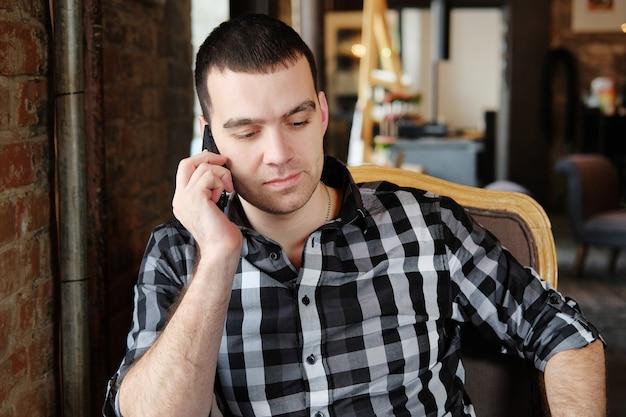 Zakenman houdt een digitale tablet en zit in een café.