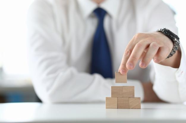 Zakenman houdt een houten kubus in zijn hand en bouwt een piramide.
