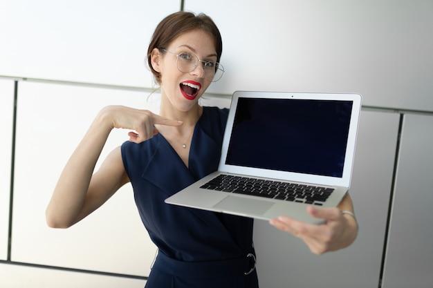 Zakenman houdt een laptop in zijn handen, toont een vinger op het scherm, mockup