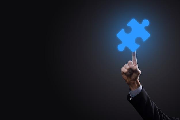 Zakenman houdt een puzzelstukje in zijn handen