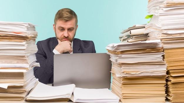 Zakenman houdt een videoconferentie op kantoor en stapels papierwerk, hij wordt overladen met werk - imago