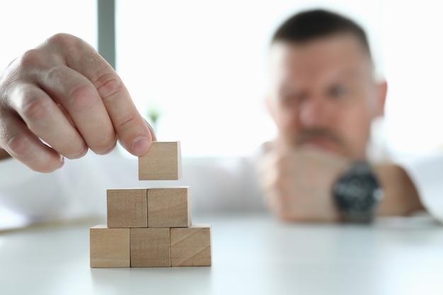 Zakenman houdt houten kubussen in zijn handen en bouwt een piramide.