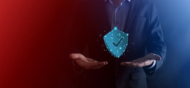 Zakenman houdt laag poly veelhoekschild met een teekpictogram. veilig toegangssysteemconcept. zakelijke financiële garantie voor investeringen. antivirusconcept. technologiebeveiliging. beschermingsnetwerk, veilige gegevens.