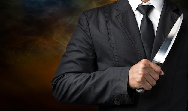 Zakenman houdt mes vast in concept van zakelijk verraden