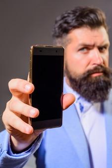 Zakenman houdt smartphone zakelijke communicatie internet technologie concept zakenman show