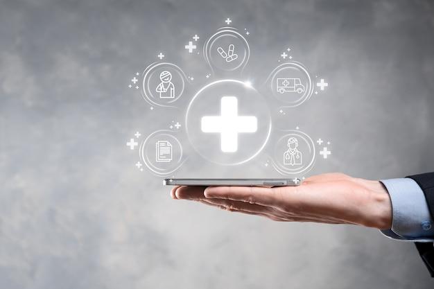 Zakenman houdt virtuele plus medische netwerkverbindingspictogrammen. covid-19 pandemie maakt mensen bewust en verspreidt aandacht over hun gezondheidszorg. arts, document, medicijn, ambulance, patiëntpictogram.