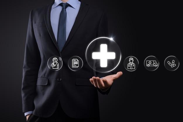 Zakenman houdt virtuele plus medische netwerkverbindingspictogrammen vast. covid-19 pandemie ontwikkelt het bewustzijn van mensen en verspreidt de aandacht op hun gezondheidszorg. arts, document, geneeskunde, ambulance, patiëntpictogram.