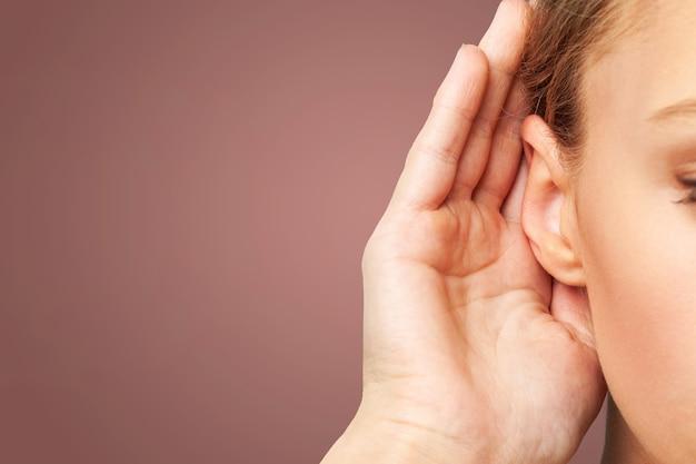 Zakenman houdt zijn hand bij zijn oor en luistert iets