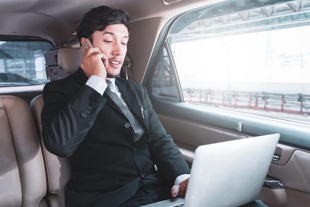 Zakenman in auto, die op laptop computer en mobiele telefoon werkt, altijd en overal werken