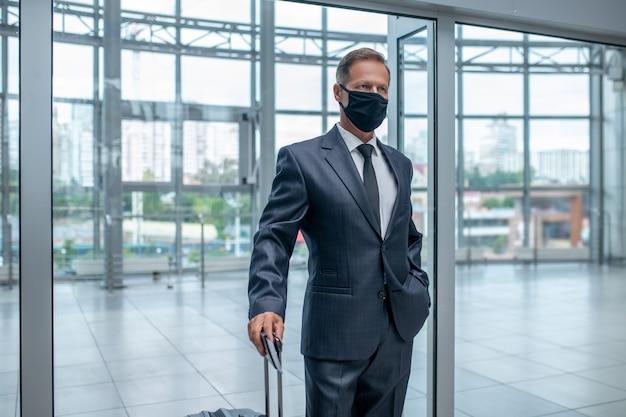 Zakenman in beschermend masker met koffer
