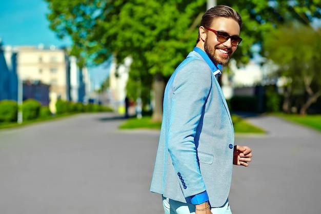 Zakenman in blauw pak dragen van een zonnebril in de straat