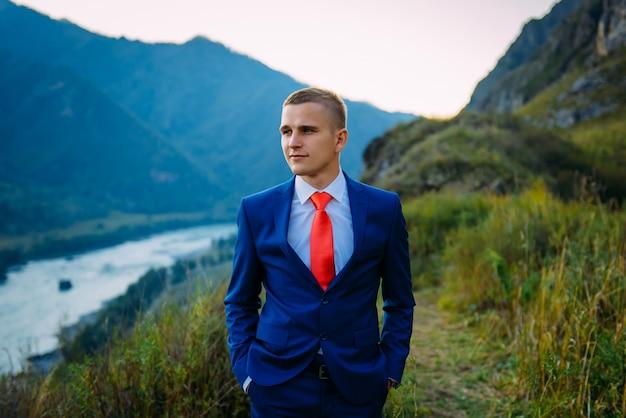 Zakenman in blauw pak met rode stropdas bovenop de wereld met achtergrond van bergen