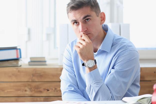 Zakenman in blauw shirt is verveeld en verdrietig