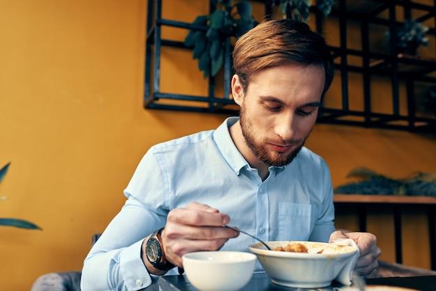 Zakenman in blauw shirt lunchen aan de tafel van een café