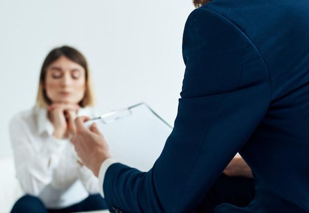 Zakenman in blauwe jas en vrouwen op de achtergrond aan de tafel