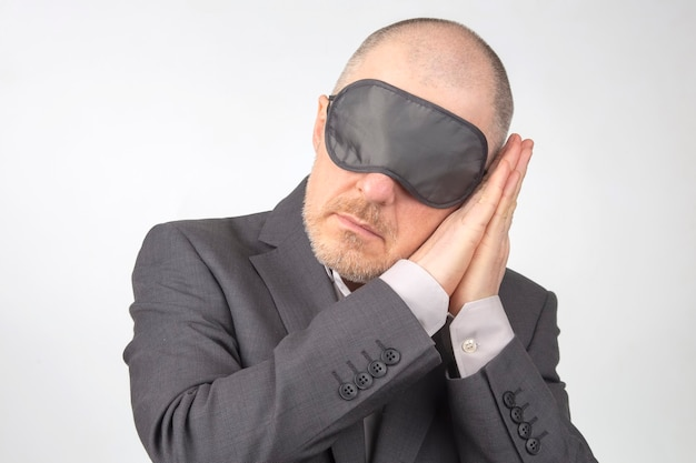 Zakenman in blinddoek om te slapen met opgeheven armen voor rust