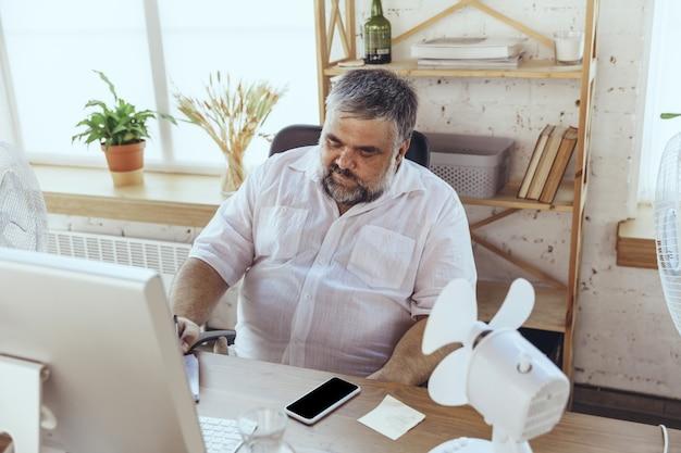 Zakenman in bureau met computer en ventilator die afkoelen, heet, gespoeld voelen
