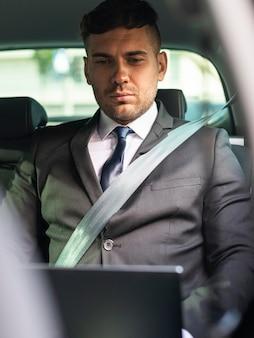 Zakenman in de auto die aan laptop werkt
