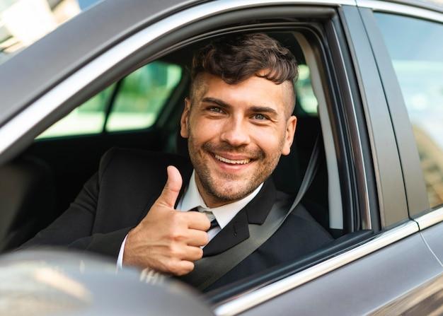 Zakenman in de auto duimen omhoog