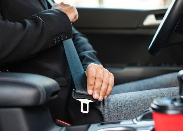 Zakenman in de auto met behulp van de veiligheidsgordel
