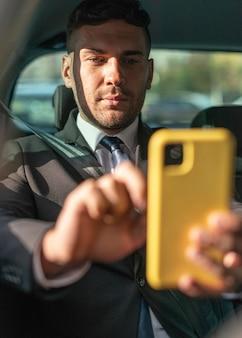 Zakenman in de auto met behulp van mobiele telefoon