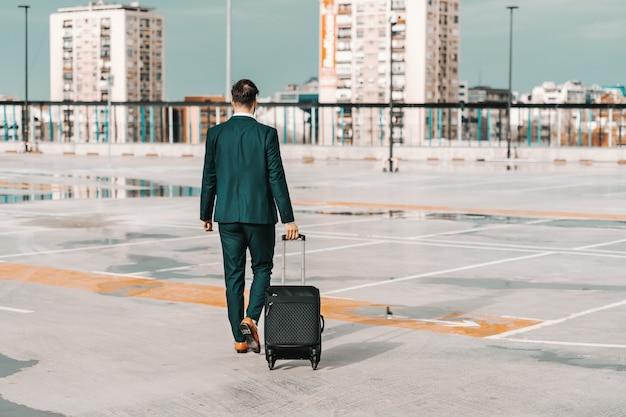 Zakenman in de bagage van de formele slijtageholding en het lopen op het parkeren. reizen bedrijfsconcept.